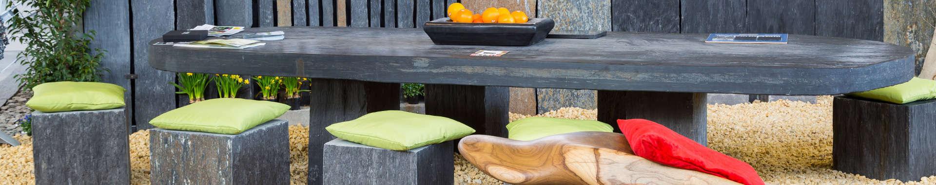 Eine Sitzgruppe mit Bänken und Stühlen aus Natursteinen