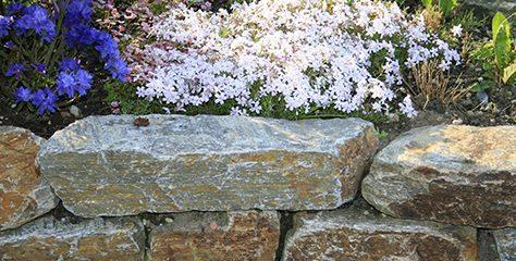 Nutzen Sie Mauersteine zum Eingrenzen Ihrer Blumenbeete