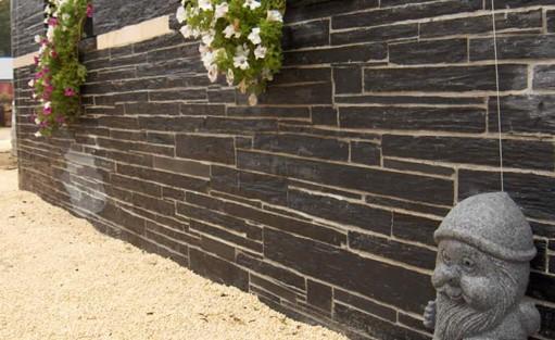 Eine Mauer aus Naturstein mit Kieseln als optische Trenner